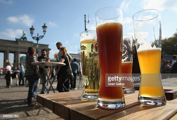 Visitors enjoy beer on German Unity Day at the Brandenburg Gate on October 3 2014 in Berlin Germany Germany is celebrating the 24th anniversary of...
