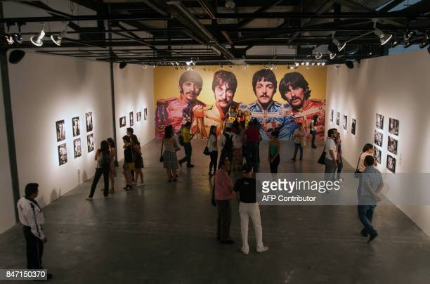 Visitors enjoy British photographer Michael Cooper exhibition on The Beatles' Sgt Pepper Lonely Hearts Club band within celebrations for the 50th...
