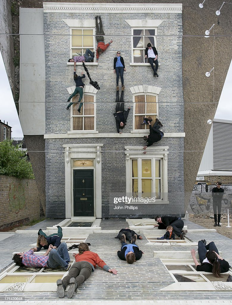 Visitors enjoy Dalston House by Argentine artist Leandro Erlich on June 24, 2013 in Hackney, London. Commissioned by the Barbican Centre Erlich has created another of his illusory installations, this time of the facade of a late Victorian terraced house, and with the aid of a mirrored surface it looks as if visitors are scaling the life-size construction.