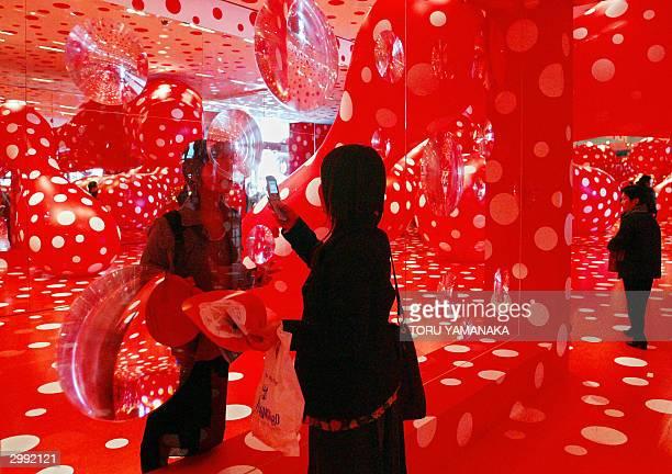Visitors enjoy 'Kusamatrix' which incorporates polkadot paintings balloons and mirrors by Japanese contemporary artist Yayoi Kusama at the Mori Art...
