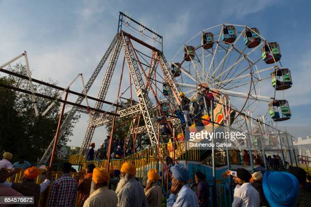 Visitors enjoy ride on a giant wheel at a fair during Hola Mohalla festival Hola Mohalla is a threeday festival started by the tenth Sikh Guru Govind...
