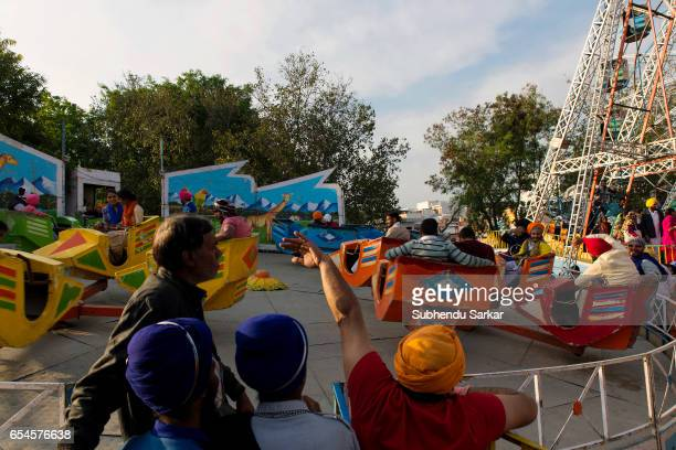 Visitors enjoy ride on merrygoround at a fair during Hola Mohalla festival Hola Mohalla is a threeday festival started by the tenth Sikh Guru Govind...
