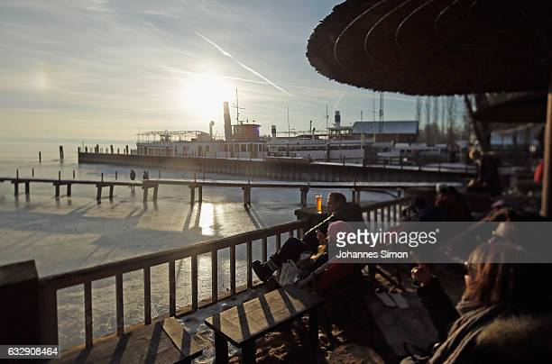 Visitors enjoy sitting in the sun in front of Lake Ammersee on January 28 2017 in Stegen am Ammersee Germany After an unusual cold winter period...