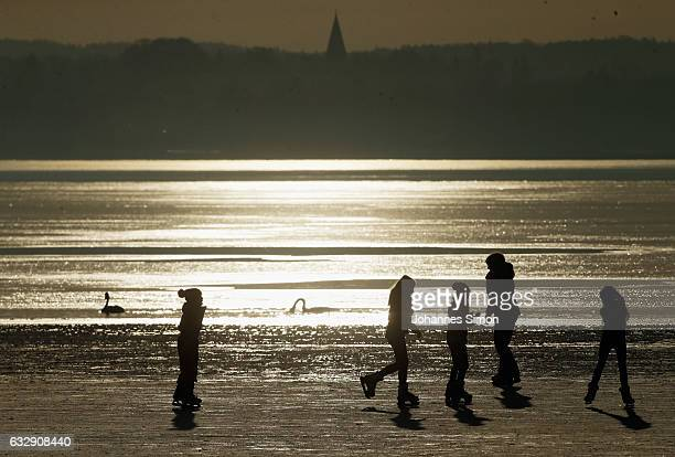 Visitors enjoy skating on Lake Ammersee on January 28 2017 in Stegen am Ammersee Germany After an unusual cold winter period currently most of the...