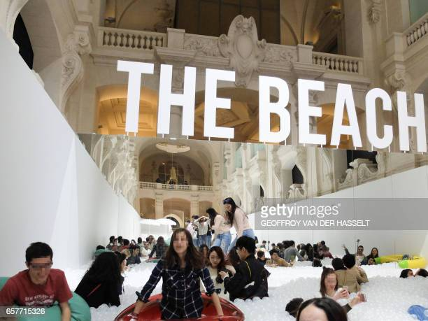 Visitors enjoy the ball pit at 'The beach' an interactive art installation that was designed by New Yorkbased collective Snarkitecture and installed...