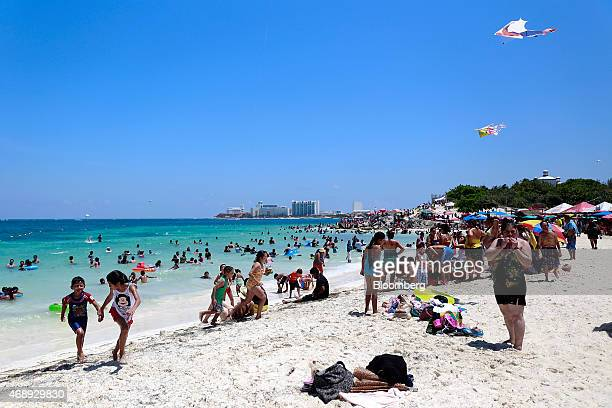 Visitors enjoy the beach in Cancun Mexico on Saturday April 4 2015 International tourists exceeded 142 million in 2014 while visitors increased 28...