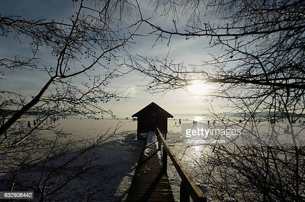 Visitors enjoy the frozen Lake Ammersee on January 28 2017 in Stegen am Ammersee Germany After an unusual cold winter period currently most of the...