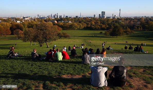 Visitors enjoy the view from Primrose Hill on October 28 2014 in London England Warmer than usual weather has seen London temperatures rise to as...