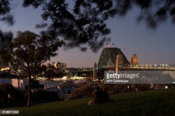 Visitors enjoy the view of Sydney's iconic landmark Harbour Bridge at sunset on July 19 2017 / AFP PHOTO / SAEED KHAN