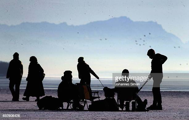 Visitors enjoy walking on Lake Ammersee on January 28 2017 in Stegen am Ammersee Germany After an unusual cold winter period currently most of the...