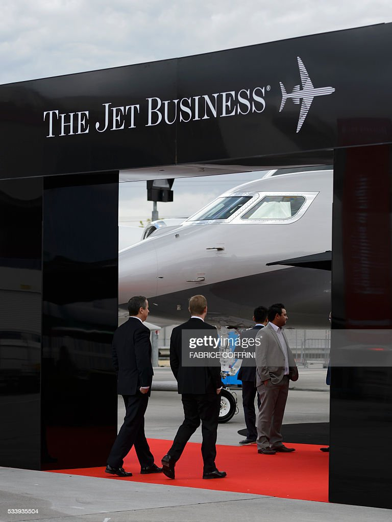 Visitors enter a stand of 'The Jet Business' during the European business aviation show EBACE (European Business Aviation Convention & Exhibition) on May 24, 2016 in Geneva. / AFP / FABRICE