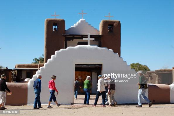 Visitors enter St Jerome Church in Taos Pueblo an ancient Native American community near the modern city of Taos New Mexico The pueblo's historic St...