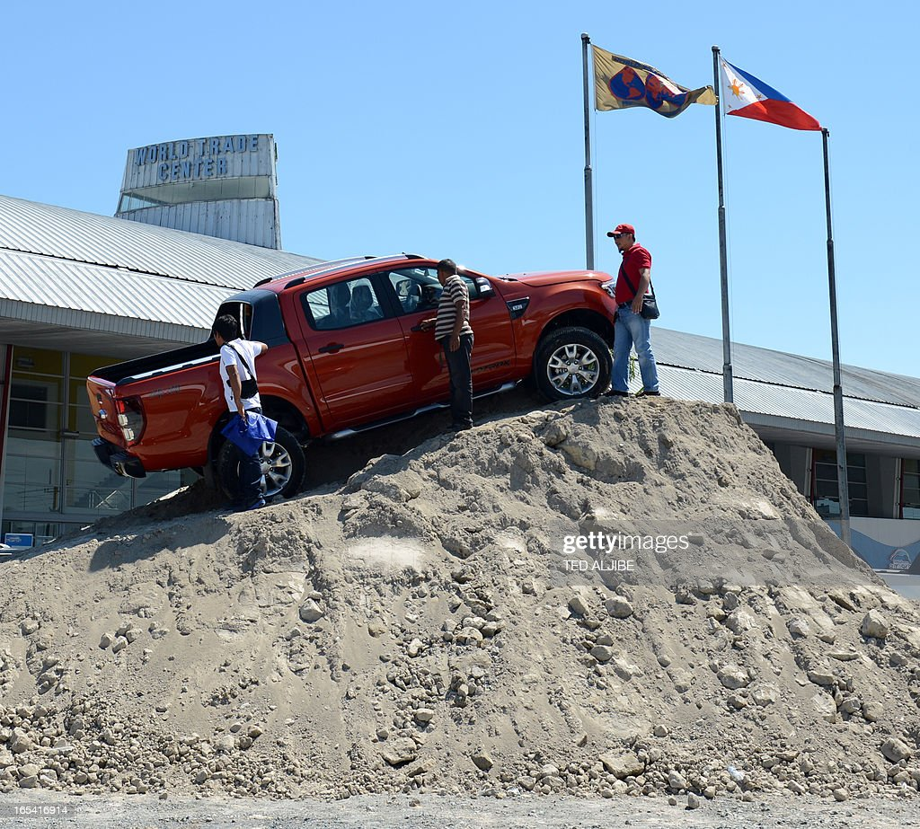 Visitors examine a 4x4 Ford ranger wildtrak displayed at a makeshift mound at the auto show in Manila on April 4, 2013. The annual auto show is being held from April 4 to 7 at the world trade center. AFP PHOTO/TED ALJIBE