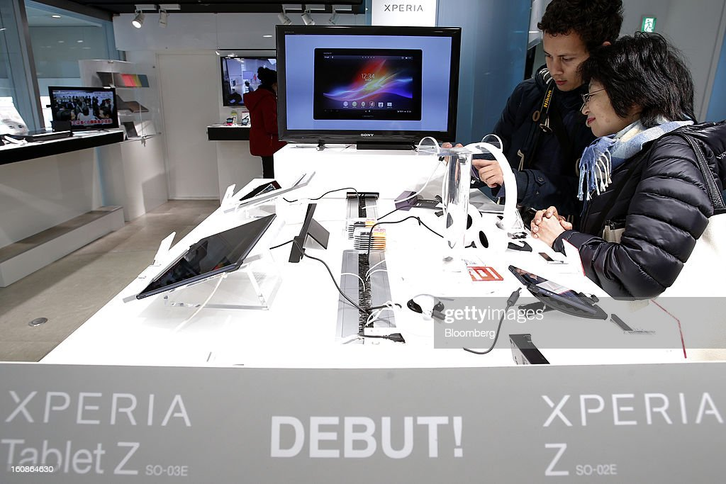 Visitors examine an Xperia Z SO-02E smartphone, manufactured by Sony Corp., while Xperia Tablet Z SO-03E tablet computers, left, sit on display at the company's showroom in Tokyo, Japan, on Thursday, Feb. 7, 2013. Sony, Japan's biggest consumer-electronics exporter, reported an eighth consecutive quarterly loss on waning demand for TVs and consumer preferences for devices from Apple Inc. and Samsung Electronics Co. Photographer: Kiyoshi Ota/Bloomberg via Getty Images