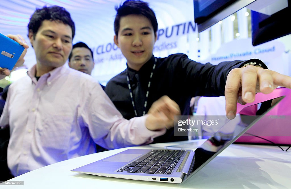 Visitors examine the Asustek Computer Inc. Asus Zenbook Prime laptop computer in the Asustek booth at Computex Taipei 2012 in Taipei, Taiwan, on Tuesday, June 5, 2012. Computex Taipei 2012 takes place from June 5 to June 9. Photographer: Ashley Pon/Bloomberg via Getty Images