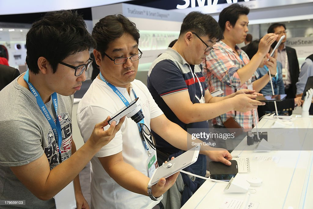 Visitors examine the Pad 8.3 tablet computer at the LG stand at the IFA 2013 consumer electronics trade fair on September 5, 2013 in Berlin, Germany. The 2013 IFA will be open to the public from September 6-11.