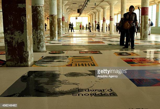 Visitors examine 'Trace' an installation by Chinese artist Ai WeiWei's that is part of @Large Ai WeiWei exhibit on Alcatraz on September 27 2014 in...