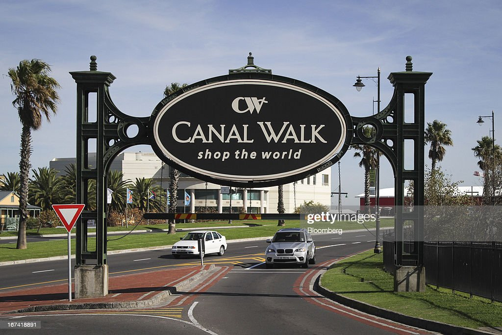 Visitors exit the Canal Walk shopping center, operated by Hyprop Investments Ltd., in Cape Town, South Africa, on Wednesday, April 24, 2013. South Africa's gross domestic product is forecast to expand 2.6 percent this year, compared with 2.5 percent in 2012, according to the country's central bank. Photographer: Nadine Hutton/Bloomberg via Getty Images