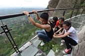 Visitors experience a 180meter long and 300meter high musical glass plank road at Shiniuzhai scenic spot in Pingjiang County on May 27 2015 in...