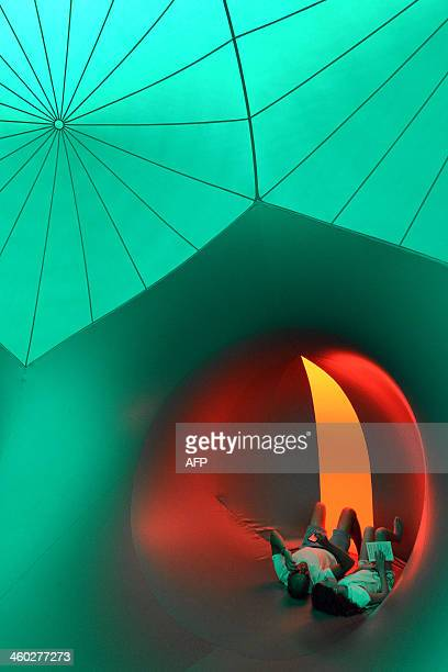 Visitors explore the inside of the Exxopolis inflatable walkin sculpture at the Opera House in Sydney on January 3 2014 The Exxopolis by Architects...