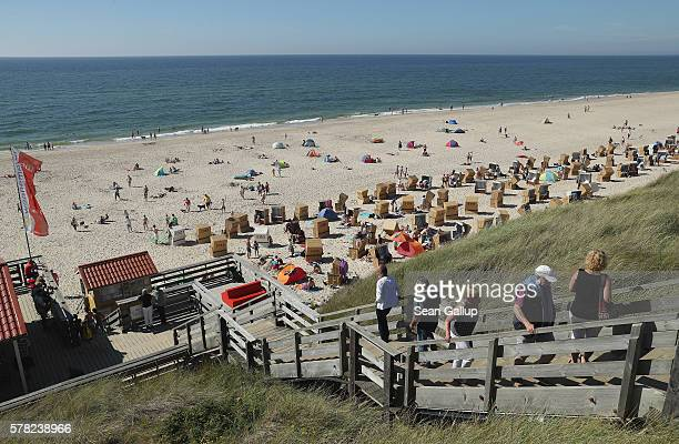 Visitors flock to a beach on Sylt Island on July 19 2016 near Wenningstedt Germany Sylt Island with its long stretches of sand beaches and its...