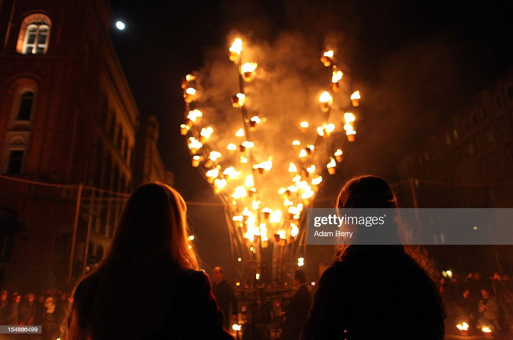 Visitors from Russia watch as an animated metal frame shaped like a flower covered in flowerpots full of flames opens and closes during a presentation by the French fire performers Carabosse as part of celebrations marking the 775th anniversary of the city of Berlin on October 28, 2012 in Berlin, Germany. The settlement of Coelln, which stood opposite Berlin on the Spree river, is first referred to in a document from 1237, and by the beginning of the 14th century Coelln and Berlin joined together to become the region's most important trading center.