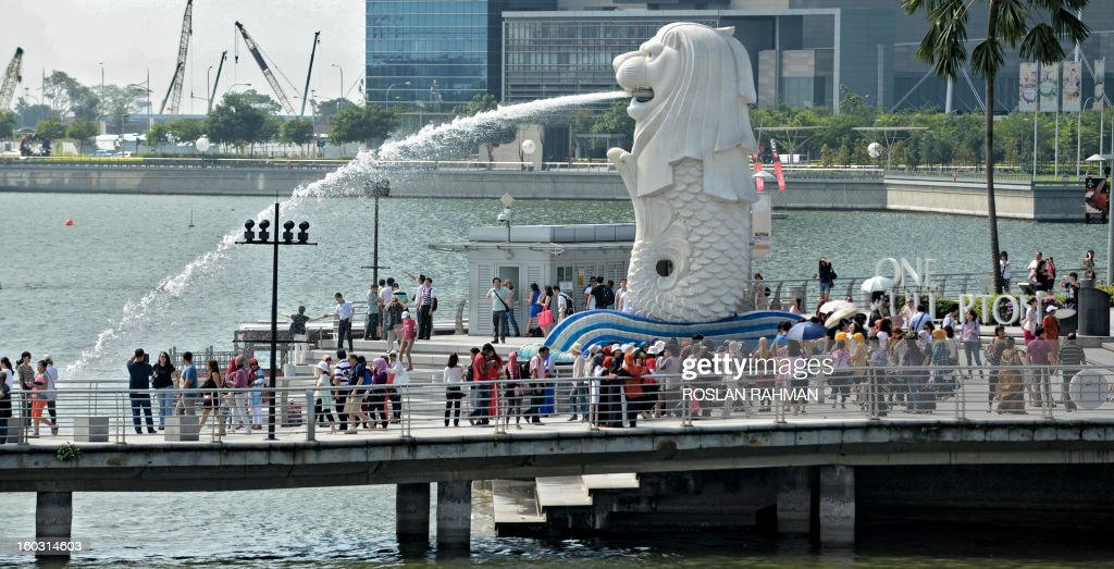 Visitors gather along the pier in front of the iconic sculpture of the Merlion in Singapore on January 29, 2013. Asia's tourism industry must prepare for major changes in the next 20 years, including a projected boom in travel by senior citizens and female business executives, a study said January 29 .