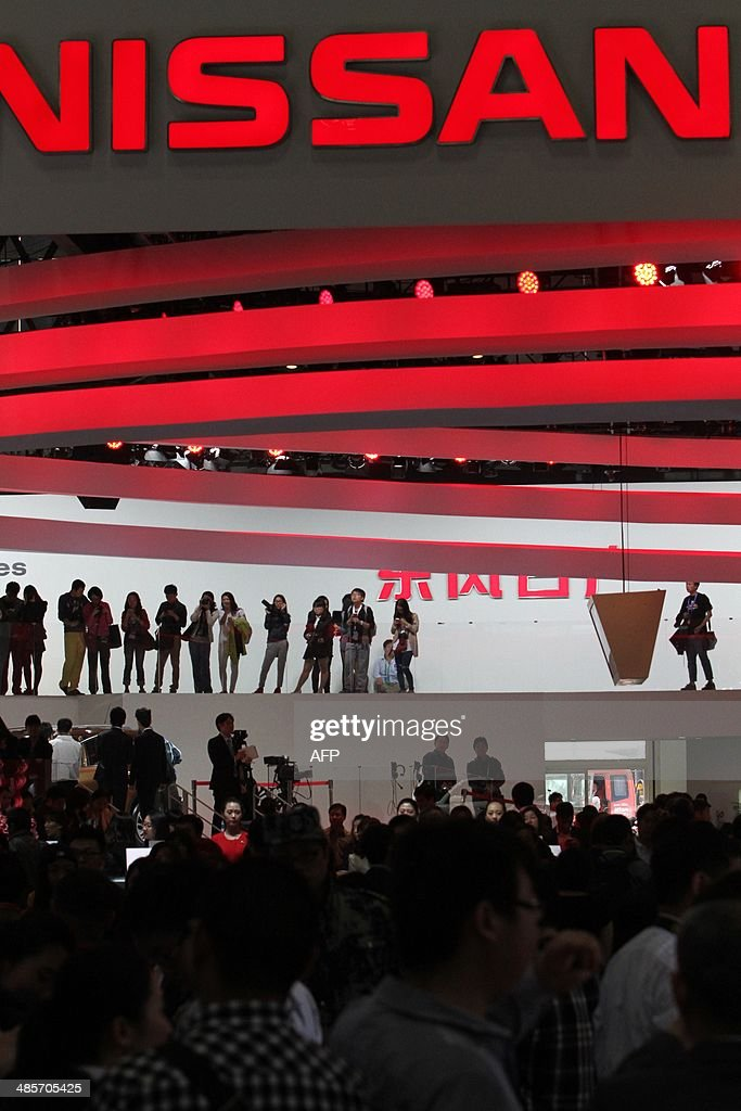 Visitors gather at the exhibition hall of Nissan at the China International Exhibition Center new venue during the 'Auto China 2014' Beijing International Automotive Exhibition in Beijing on April 20, 2014. Leading automakers are gathering in Beijing for the kickoff of China's biggest car show, but lackluster growth and environmental restrictions in the world's largest car market have thrown uncertainty into the mix. More than 1,100 vehicles are being showcased at the auto show, which opens to the public on April 21. CHINA