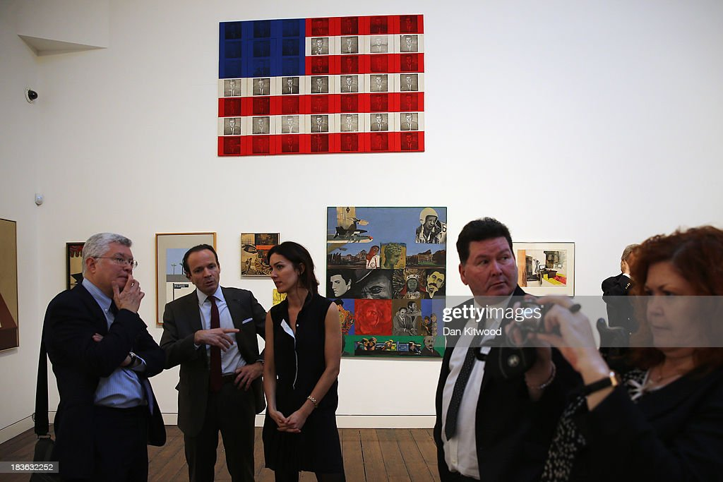 Visitors gather beneath a piece of work entitled 'JFK' by Billy Apple during the 'When Britain went Pop!' exhibition at Christie's auction house on October 8, 2013 in London, England. The exhibition claims to be 'the first ever Comprehensive exhibition of British Pop Art to be held in London' and includes work by artists including David Hockney, Peter Blake, Richard Hamilton and Allen Jones and opens to the public until November 23.