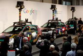 Visitors gather in front of German Google Street View cars at the Google stand at the CeBIT Technology Fair on March 3 2010 in Hannover Germany...