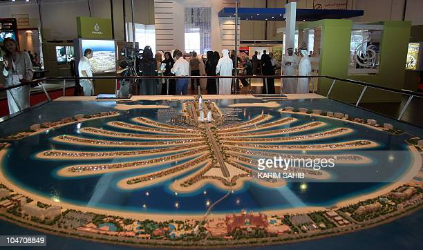 visitors gather near the stand of the real estate giant Nakheel the developer behind Dubai's iconic palmshaped manmade islands at the Cityscape...