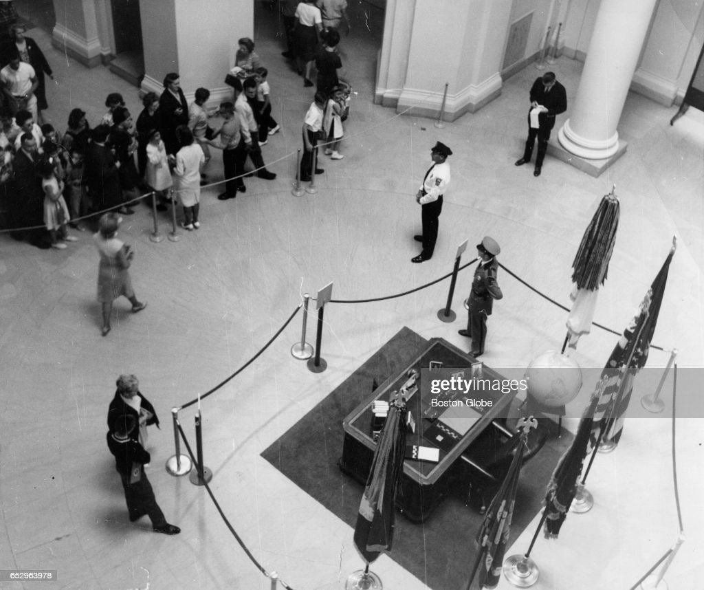 Visitors gather outside ropes to view the desk used by the late President Kennedy at the traveling John F. Kennedy Library Exhibit at the Museum of Fine Arts in Boston on Aug. 19, 1964.