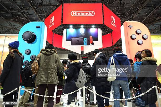 Visitors gather to play Nintendo's new Switch game console during its game experience session in Tokyo on January 14 2017 Nintendo on January 13...