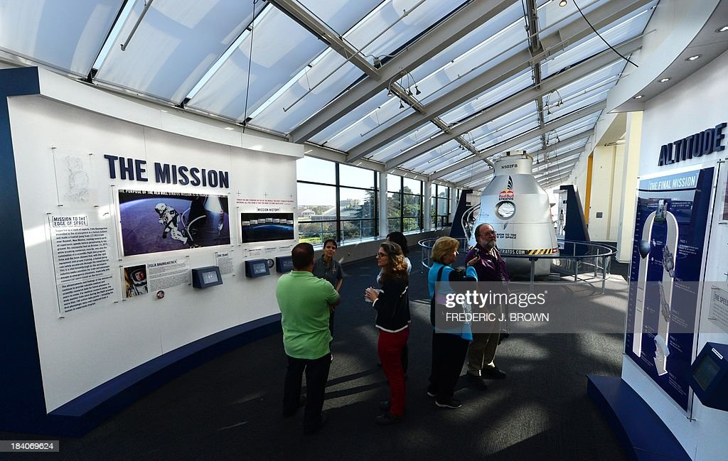Visitors gather to read or hear about the mission of the Red Bull Stratos on exhibit at the California Science Center during a media preview ahead of the opening of Endeavour Fest, commemorating the one-year anniversary of the Space Shuttle Endeavour's arrival in Los Angeles, on October 11, 2013 in California. While visitors to the three-day exhibition will also see a SpaceX Dragon spacecraft as well as the west coast launch of the Red Bull Stratos Exhibit, the lack of funding to NASA due to the government shutdown precludes their participation in Endeavour Fest, as NASA will not be able to provide exhibits or displays for the event and the NASA scientist presentations will be cancelled AFP PHOTO/Frederic J. BROWN