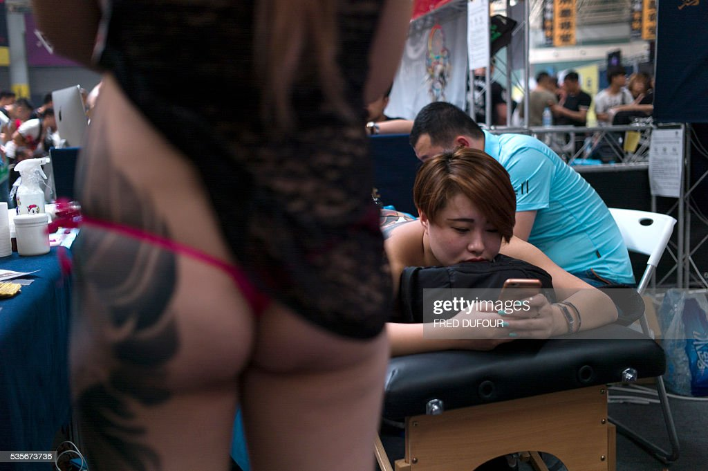 Visitors gather to watch a chinese woman get a tattoo on her legs at the Langfang International Tattoo show, in Hebei province, on May 29, 2016. / AFP / FRED