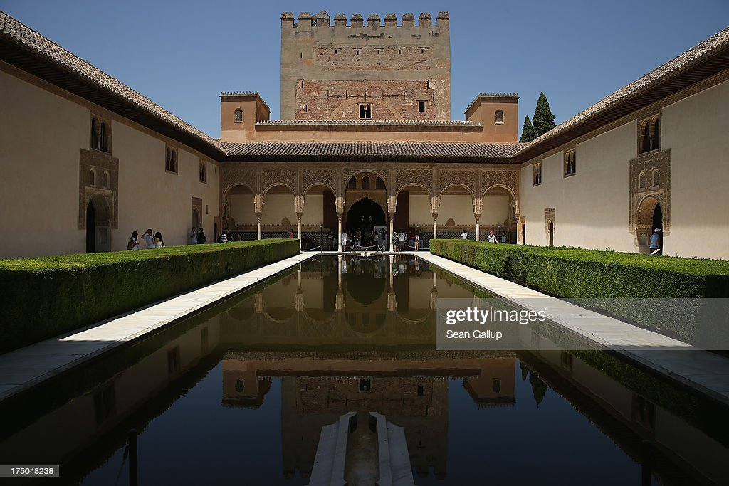 Visitors gaze at the reflecting pool in the Court of the Myrtles in the Nasrid Palaces at the Alhambra on July 23 2013 in Granada Spain Southern...