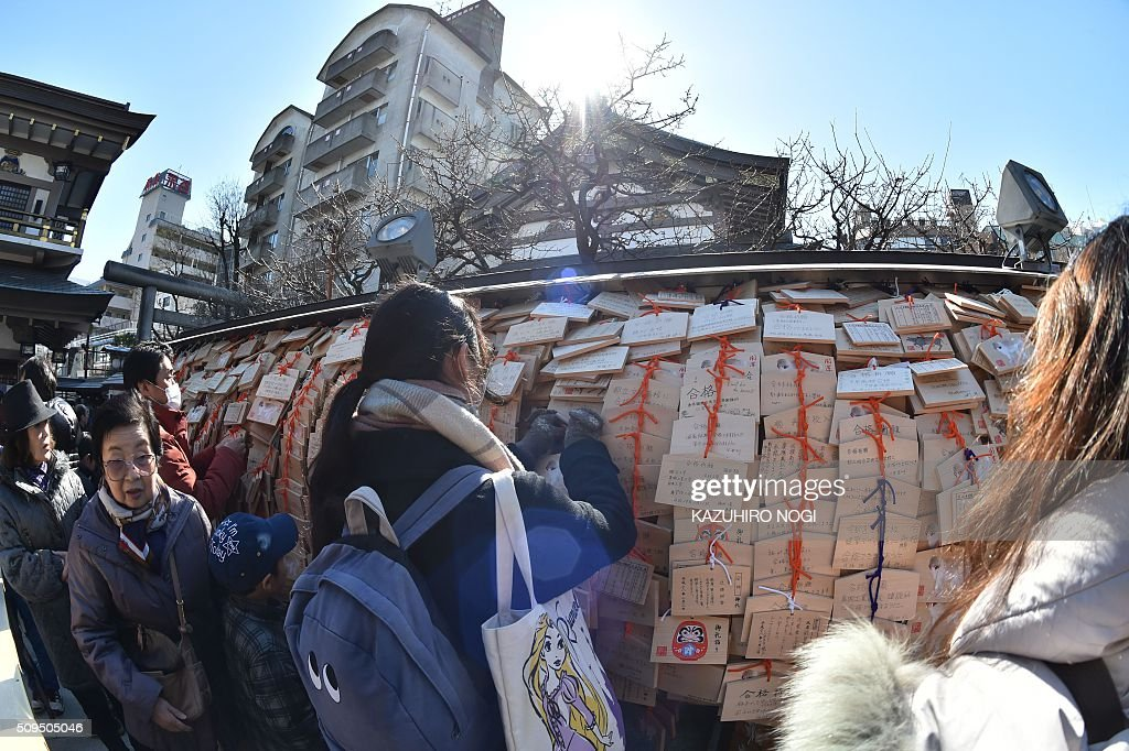 Visitors hang small wooden votive tablets after writing their wishes on them, at Yushima Tenjin shrine in Tokyo on February 11, 2016. Every year many students and their parents come to the shrine to pray for success at exam time as the annual school entrance examination season started. AFP PHOTO / KAZUHIRO NOGI / AFP / KAZUHIRO NOGI