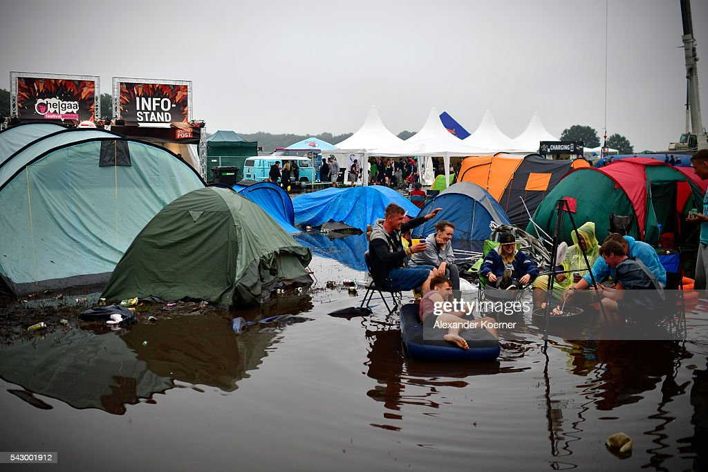 Visitors have fun while sitting and one lies on an inflatable mattress at the flooded camping compound at the Hurricane Festival compound on June 25, 2016 in Scheessel, Germany. The Hurricane Festival was evacuated yesterday and was delayed today for the late evening, following heavy rain and thunderstorm alerts. The rain and thunderstorm have hit the festival during the night and day, causing damage to tents and flooded the festival site, only 7 concerts can be played on two stages today. The Hurricane Festival celebrates this year its 25th anniversary. 75.000 music fans have visited the Festival, but some thousands have already left the compound due to the current situation.