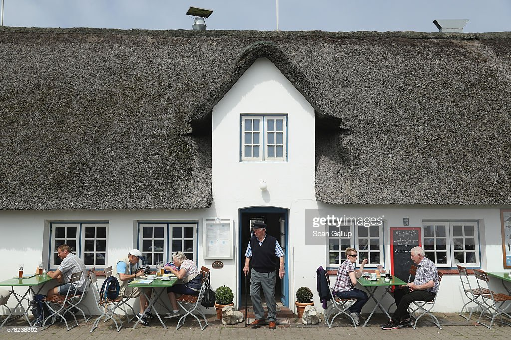 Visitors have lunch at a restaurant with a thatched roof on the Hamburger Hallig peninsula on July 19, 2016 near Bordelum, Germany. Hamburger Hallig is a protected national park and a favorite destination for vacationers along Germany's North Sea coast. Many Germans, unsettled by the recent terror attacks in countries like France and Turkey, are choosing to vacation in Germany this summer.