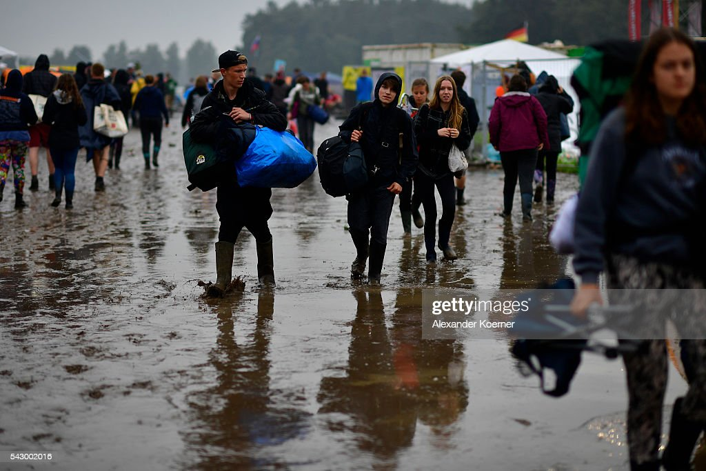Visitors have packed up and leave the muddy camping compound at the Hurricane Festival compound on June 25, 2016 in Scheessel, Germany. The Hurricane Festival was evacuated yesterday and was delayed today for the late evening, following heavy rain and thunderstorm alerts. The rain and thunderstorm have hit the festival during the night and day, causing damage to tents and flooded the festival site, only 7 concerts can be played on two stages today. The Hurricane Festival celebrates this year its 25th anniversary. 75.000 music fans have visited the Festival, but some thousands have already left the compound due to the current situation.