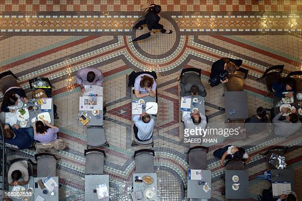 Visitors have their lunch inside a shopping arcade in the Central Business District of Sydney on April 3 2013 Australia's central bank kept interest...