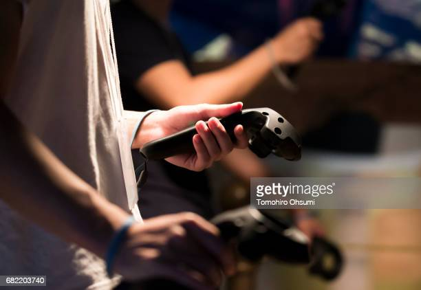 Visitors hold controllers as they play the Salomon's Carpet VR virtual reality video game at the VR Park Tokyo on May 12 2017 in Tokyo Japan The VR...