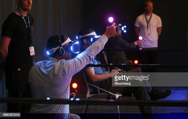 Visitors hold illuminated controllers while wearing prototypes of the Sony Project Morpheus virtual reality gaming headset at the Sony Corp...
