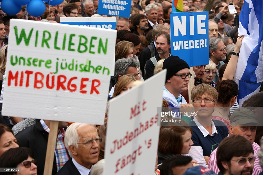 Visitors hold signs reading 'We Love Our Jewish Fellow Citizens' and 'Never Again' in German during a rally against antiSemitism on September 14 2014...