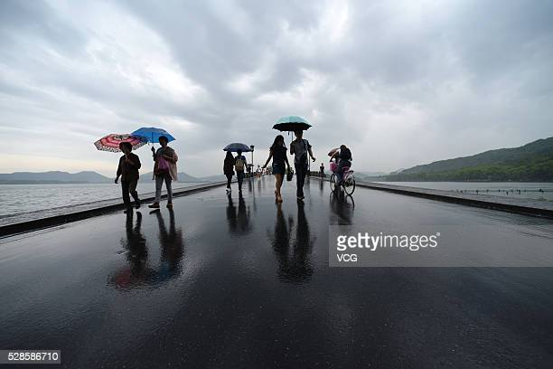 Visitors hold umbrellas while walking on the Broken Bridge at West Lake on May 5 2016 in Hangzhou Zhejiang Province of China Hangzhou welcomed an...