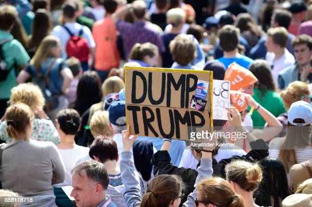 Visitors hold up a banner 'Dump Trump' prior the arrival of former President of the United States of America Barack Obama and German chancellor...
