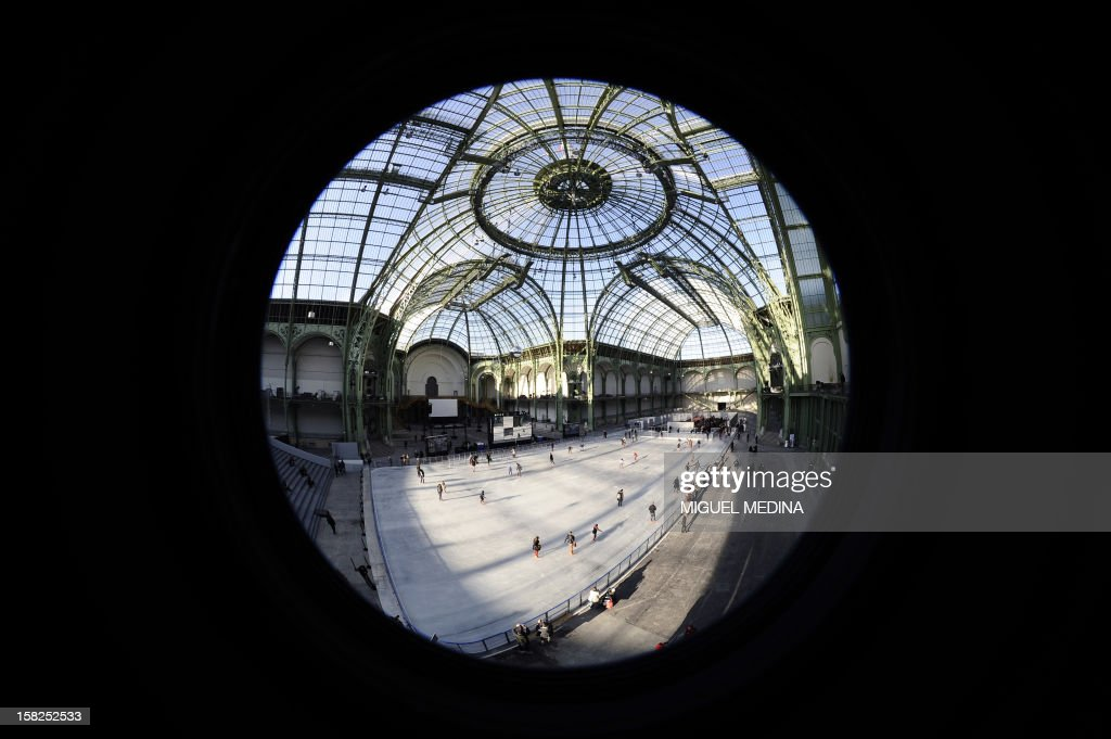 Visitors ice-skate on a giant rink hosted in the glass-roofed central hall of the Grand Palais on December 12, 2012 in Paris. At 1,800 square metres in size, it's the largest rink ever created in France. AFP PHOTO /MIGUEL MEDINA