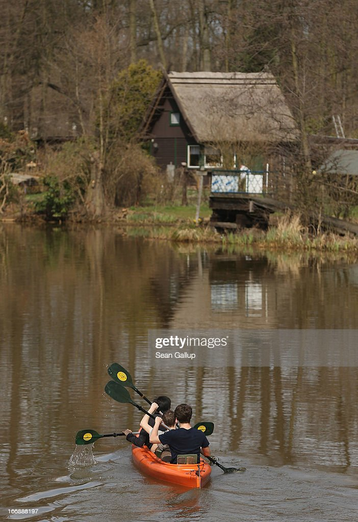 Visitors in a canoe paddle along one of the many canals on the Spreewald region on April 17, 2013 near Luebbenau, Germany. The nearby Wudritz creek is heavily burdened with iron from the nearby former Schlabendorf open pit coal mine, which has since been turned into a lake called the Schlabendorfer See. Many creeks and small rivers that feed the Spree River have turned a rich orange or brown, sometimes even red, due to the sediments flowing from several former open pit coal mines. The Spreewald is a popular tourist destination known for its network of canals and local tour operators fear the sediment will turn the waters there orange as well, which could seriously impact the tourist seasons. Though the iron sediment is not poisonous, some local farmers claim they have been forced to filter the water they use to irrigate their fields, and many people report the disappearance of fish and other fauna.