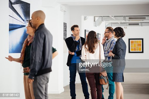 Visitors In Art Gallery Looking At Artwork And Talking