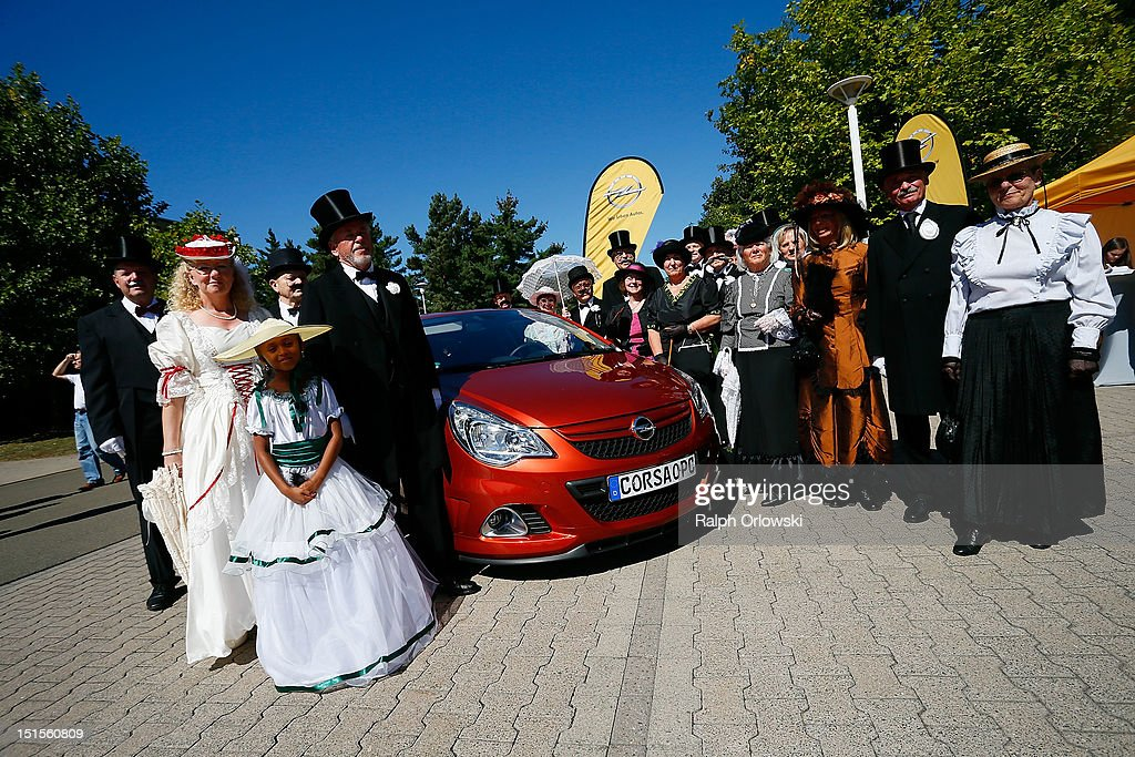 Visitors in historic costumes stand around an Opel Corsa at the manufacturing plant of German car maker Adam Opel GmbH on September 8, 2012 in Kaiserslautern, Germany. Automaker Opel, founded in 1862, celebrates their 150th anniversary.
